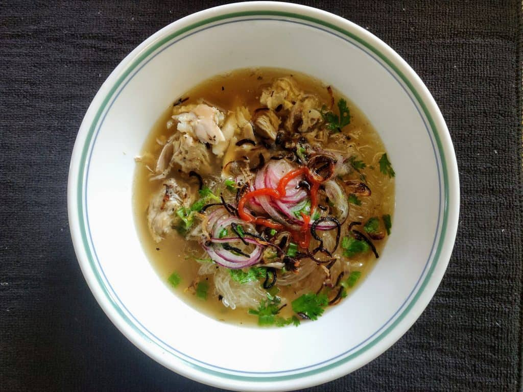 Bowl of chicken pho with heart shaped sriracha