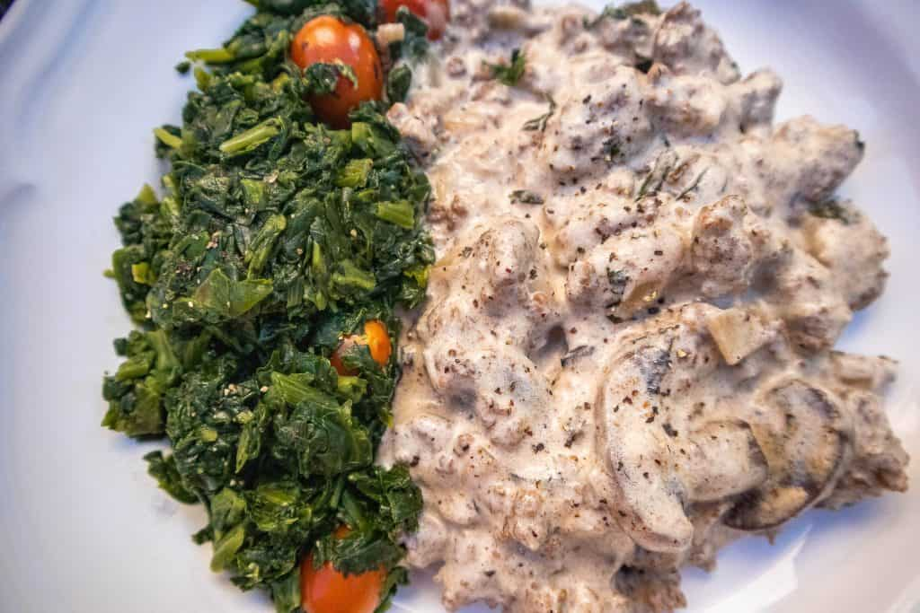 A dish of beef stroganoff with a side of saute spinach and cherry tomatoes