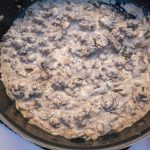 A large skillet of creamy ground beef stroganoff with mushrooms